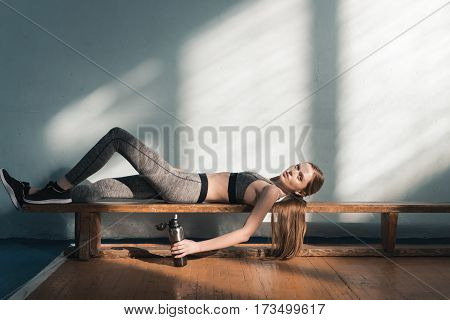 sporty woman lying on bench with sports bottle