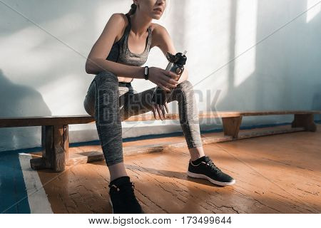partial view of sporty woman sitting on bench with bottle of water
