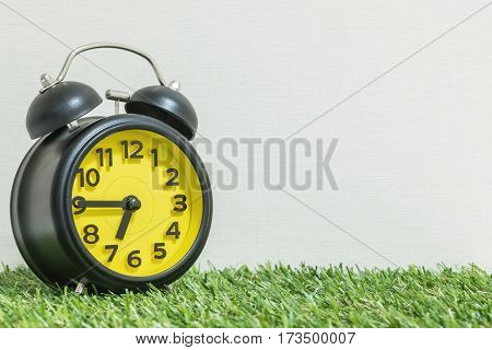 Closeup black and yellow alarm clock for decorate show a quarter to seven p.m. or 6:45 a.m. on green artificial grass floor and cream wallpaper textured background with copy space