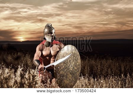 Sepia toned shot of an ancient Roman legionary soldier walking in the field on dusk holding his sword and a shield copyspace