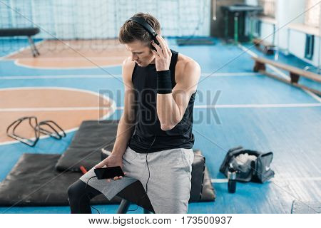 Young sporty man in headphones sitting on pommel horse and using smartphone