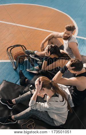 High angle view of tired young sportspeople sitting on floor in sports center