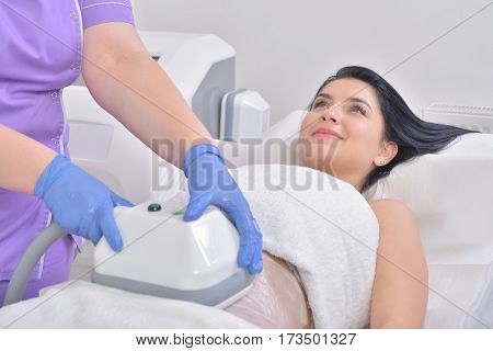 Pretty young woman getting cryolipolyse fat treatment in professional cosmetic cabinet poster