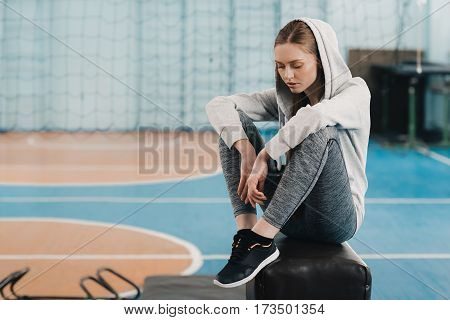 Young sporty woman sitting on pommel horse and looking down
