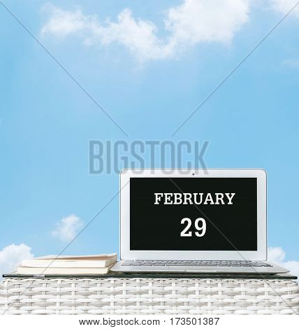 Closeup computer laptop with february 29 word on the center of screen in calendar concept on blurred wood weave table and book on blue sky with cloud textured background with copy space