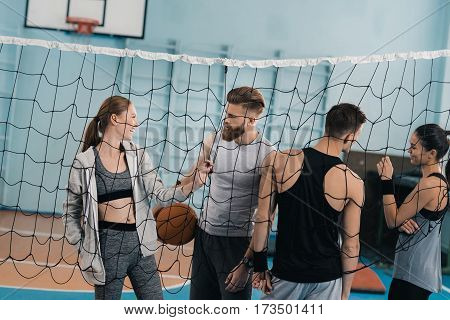 Sporty young people with ball standing near net in sports hall