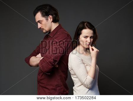 Family quarrel, man and woman standing back to each other, looking sad and displeased