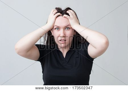 Girl in a panic bows head in his hands, thinking about problems