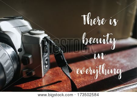 Isolated calligraphy on Camera film on brown wooden stairs. Quote about photo and photography. There is beauty in everything.
