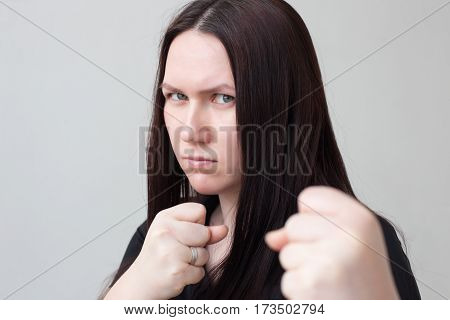 Girl clenches her fists, ready to defend and attack