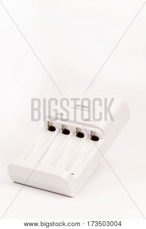 White Battery Charger Over White Background With Copy Space