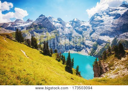 Panorama of the azure pond Oeschinensee. Popular tourist attraction. Picturesque and gorgeous scene. Location Swiss alps, Kandersteg, Bernese Oberland, Europe. Instagram toning effect. Beauty world.