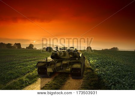 Army Tank On The Rural Path By Sunset.