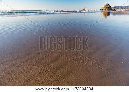 Pleasant outlook of calm sea water washing large stones near mountain covering with forest