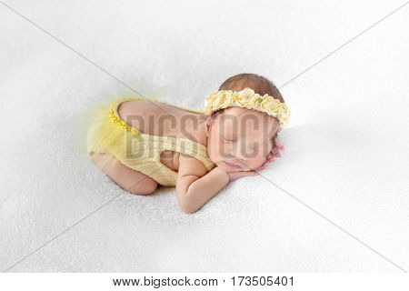 Lovely baby dressed in a yellow outfit with lowcut back sleeping on a white surface
