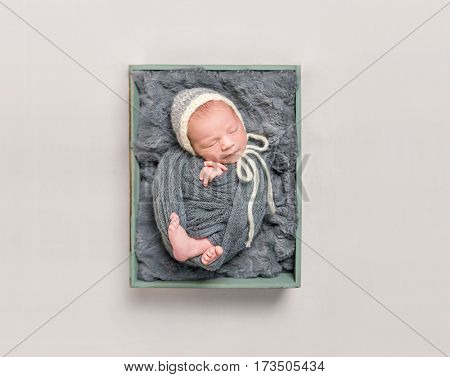 Sweet baby wrapped in a dark gray blanket resting in child's basket, topshot