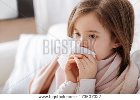 I have caught a cold. Poor ill little girl using handkerchief while recovering at home