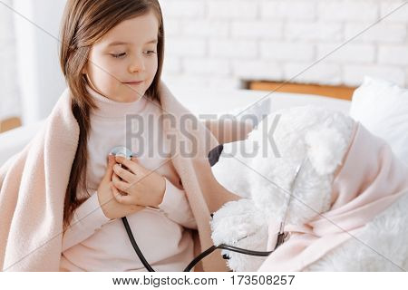 Involved in game. Positive little girl playing with her fluffy bear and sitting on the couch while pretending to be a sick patient