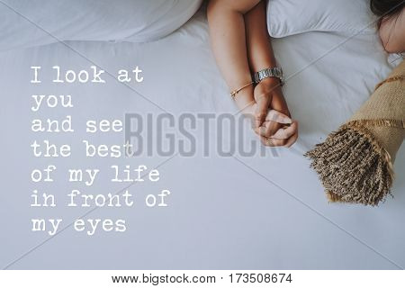 Inspirational quotes about love. Hand in hand of young couple background. I look at you and see the best of my life in front of my eyes.