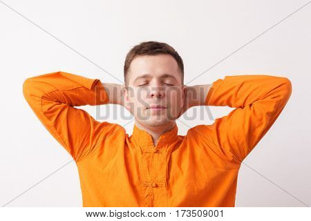 Young Man In An Orange Shirt Resting Or Meditating, Hands Behind Head