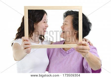 Portrait of Asian senior mother and adult daughter hands holding an empty photo frame, looking at each other, isolated on white background.