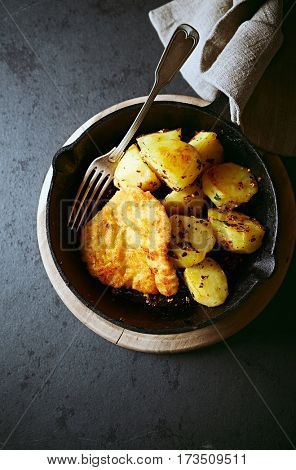 Breaded pork cutlet with potatoes on a frying pan; Polish cuisine