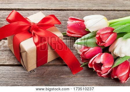 Colorful tulips bouquet and gift box on wooden background. Red and white.