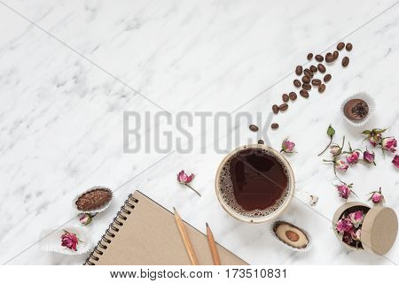 Morning composition with a cup of black coffee chocolate candies and a notebook on a marble surface with space for text top view