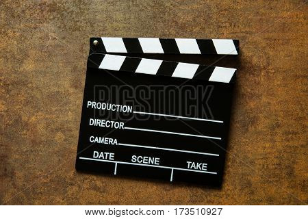 The vintage clapperboard on rusty background. Top view.