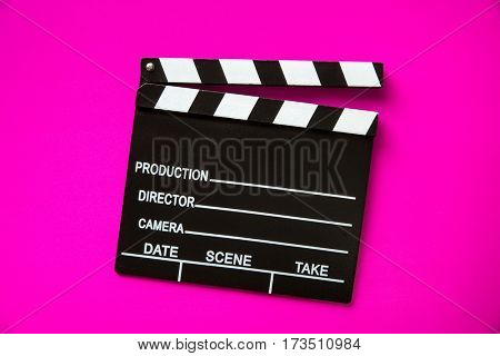 The vintage clapperboard on pink background. Top view.