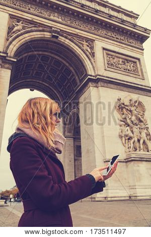 Urban girl with cellphone and Arc de Triomphe Paris France in the background.