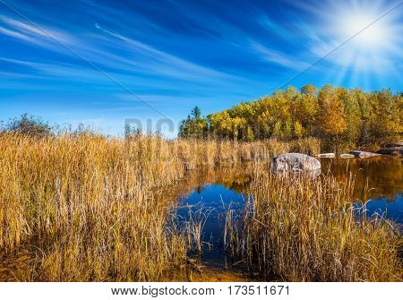 Pale northern sun and yellow autumn grass is reflected in the Winnipeg River. Old Pinawa Dam Provincial Heritage Park. The concept of travel