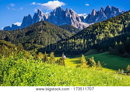 The valley Val di Funes -  picturesque little church of Santa Maddalena. Rocky peaks and forested mountains surrounded by green Alpine meadows. Sunny day in Dolomites, Tirol