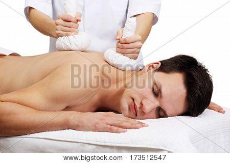 Thai Ball Massage. Man getting SPA thai herbal compress massage. Isolated on white background