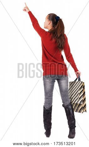 back view of  woman  in  jeans  with shopping bags pointing .   backside view of person.  Rear view people collection. Isolated over white background.