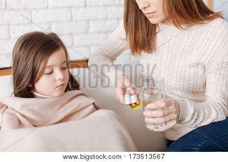 I dont want. Sick little nice girl sitting under the blanket while her mother giving her pills and helping to recover