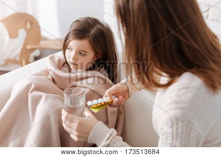 You should take it. Caring mother giving pills to her sick daughter while helping to recover and sitting on the sofa