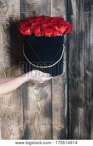 Beautiful red roses bunch of fresh natural flowers in black present box in female hands on wooden wall background