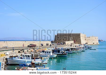 HERAKLION, CRETE - SEPTEMBER 19, 2016 - Traditional fishing boats moored in the harbour with Koules castle to the rear Heraklion Crete Greece Europe, September 19, 2016.