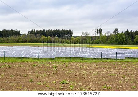 Solar battery station with blue panels standing in field at cloudy sky day