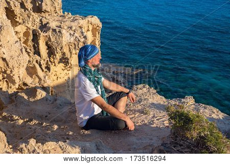 Bearded Man Traveler Meditate And Relax On A Rocky Seashore