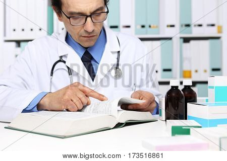 Doctor reading a Medical Book in Office Desktop. Health care Medical and Pharmacy Concept.