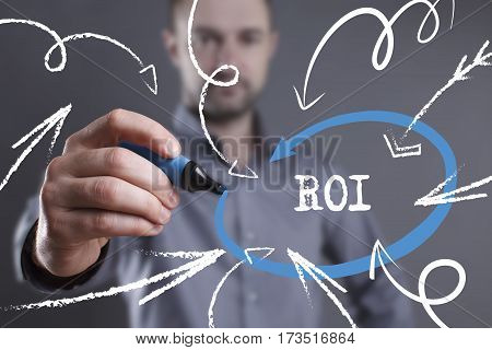 Technology, Internet, Business And Marketing. Young Business Man Writing Word: Roi