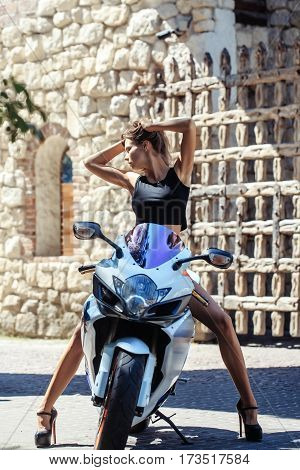 Pretty girl or sexy woman biker in black undershirt and high heels sits on motorcycle or scooter on sunny summer day outdoors on streetscape background