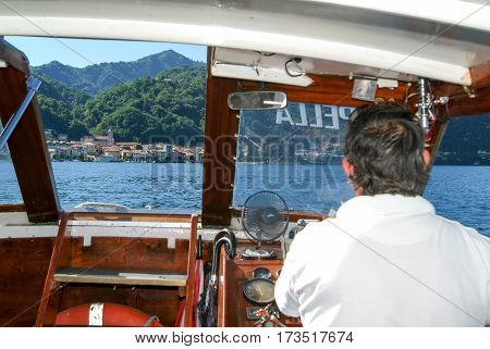 Captain Driving A Boat In Front Of Orta On Lake Orta