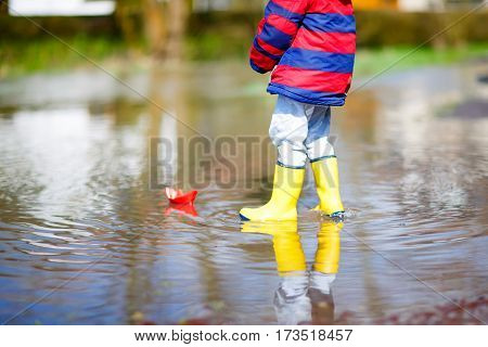 little kid boy in yellow rain boots playing with paper ship by a puddle on spring or autumn day. Active leisure for children. Child having fun outdoors and wearing colorful clothes.
