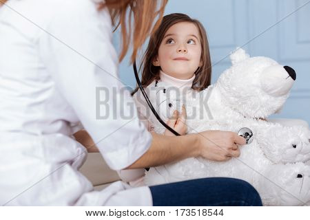 Help him. Positive little girl holding her fluffy yoy and visiting doctor while sitting on the couch