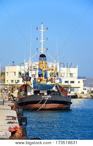 HERAKLION, CRETE - SEPTEMBER 19, 2016 - Tug boat moored in the harbour with the coastguard office to the rear Heraklion Crete Greece Europe, September 19, 2016.