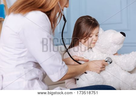 Check it out. Pleasant professional doctor using stethoscope and examining fluffy toy of littke girl while sitting together on the couch