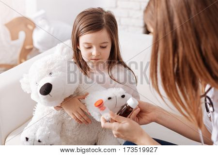 Healthy help. Cheerless little girl holding her fluffy toy and going to take pills while professional doctor giving her tipps